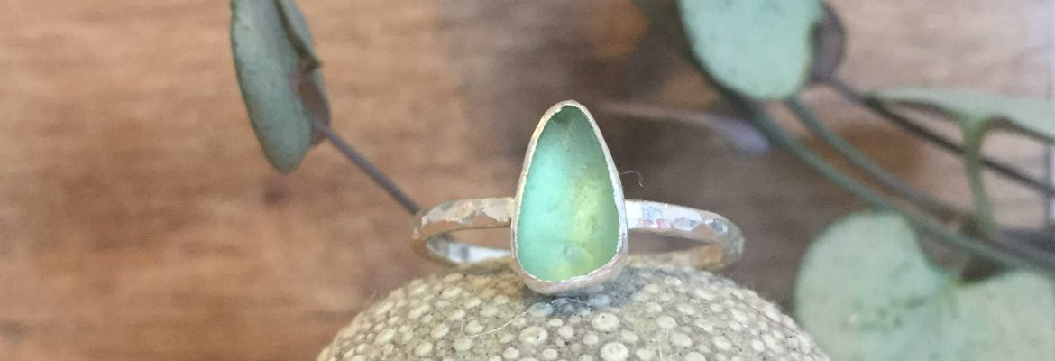 Small green tear-drop seaglass ring, sat on a sea urchin