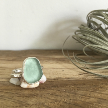 pale turquoise seaglass ring with silver stacking ring, sat on white shells.