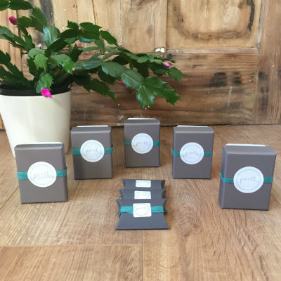 Porth packaging for necklaces and rings - grey boxes with a turquoise strip to seal and the Porth logo on the front