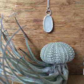 An oval white seaglass necklace with 2 circular jump rings attaching it to the chain