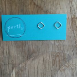 Pair of diamond stud earrings pointing 'up' on turquoise Porth earring card.