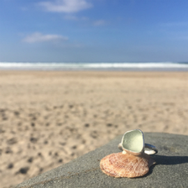 Ice-coloured seaglass ring, sat on a sheet with the sea.