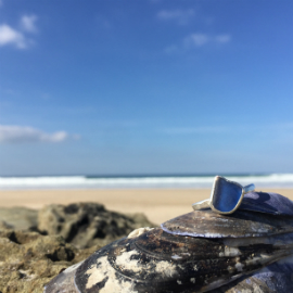 Blue seaglass ring, sat on a rock with the sea in the background