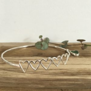 Heather's commissioned bangle. 5 silver hearts (one for each dog), attached to a silver bangle, with a green heart seaglass charm.