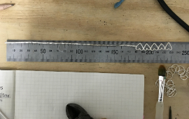 Measuring the length of Heather's commissioned bangle against a ruler.