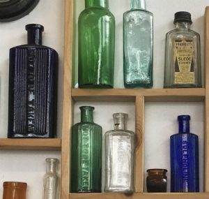 A close-up of the bottle display at Marmalade Antiques, Falmouth. Blue poison bottles.