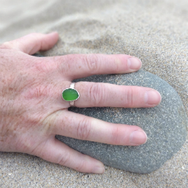 Green seaglass ring being worn on the beach. The hand is on a pebble with sand behind.
