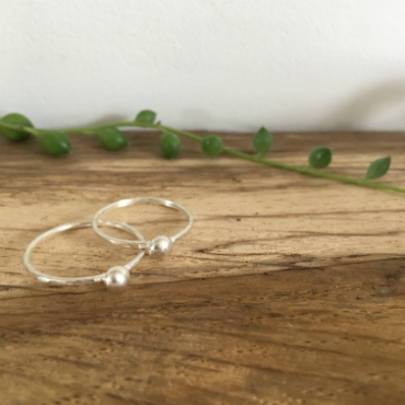 2 thin silver rings, each with a silver pebble attached.