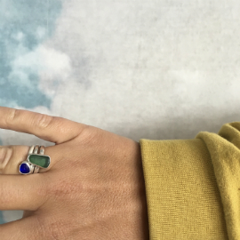 Mari's hand showing off her blue seaglass ring made in Seaglass Sessions alongside her Porth Jewellery seaglass ring.